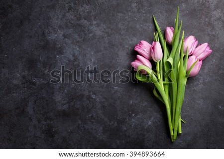 Fresh purple tulip flowers on dark stone table. Top view with copy space - stock photo