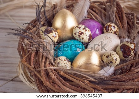 Fresh quail eggs in a nest filled with feathers on a wooden rustic background.