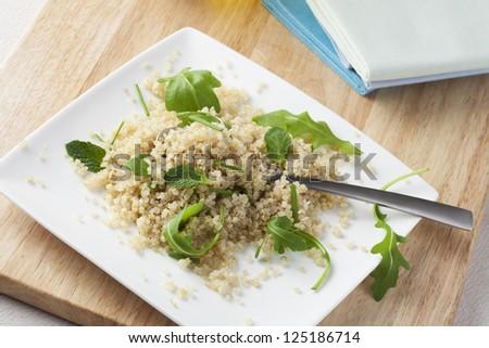 Fresh quinoa salad with herbs and arugula - stock photo