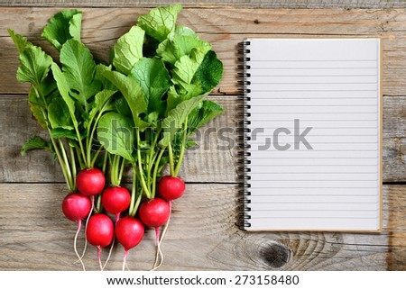 Fresh radish and recipe book on wooden background - stock photo