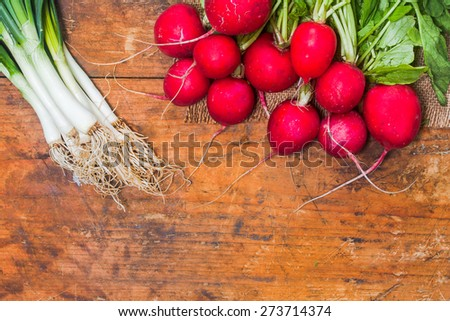 Fresh radishes and onion on old rustic wooden table - stock photo