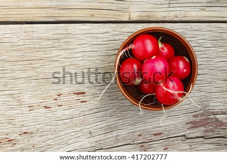 Fresh radishes in an earthenware bowl. Close-up, top view, flat layout.