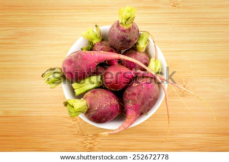 Fresh radishes in bowl against wooden background - stock photo