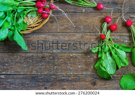 Fresh radishes on old wooden table in a wicker basket - stock photo