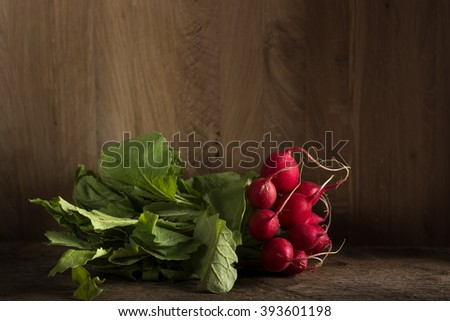 Fresh radishes on old wooden table with copy space - stock photo