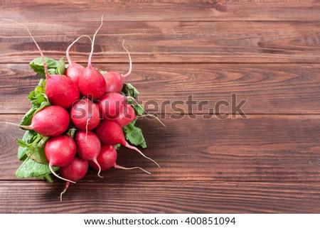 Fresh radishes on wooden background - stock photo