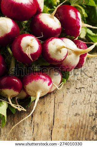 Fresh radishes with leaves on a wooden table, selective focus - stock photo