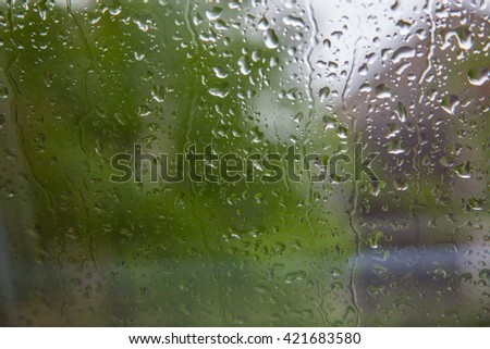 Fresh rain splash drops on a window with background green nature. Blurry background