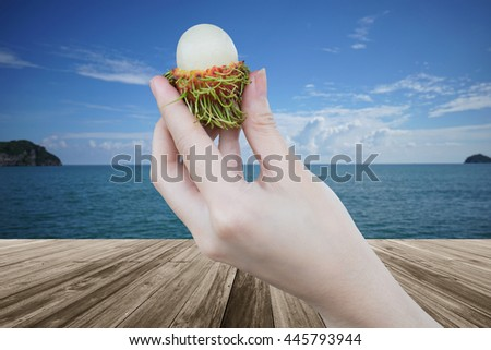 fresh Rambutan fruit in woman hand holding peeled rambutan with a perspective wooden table over blurred sea and blue sky in background - stock photo
