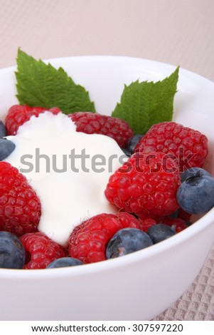 fresh raspberries and berry with cream and sugar on a bowl - stock photo