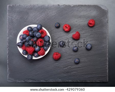 fresh raspberries  and bilberry berries scattered on black background.Top view - stock photo
