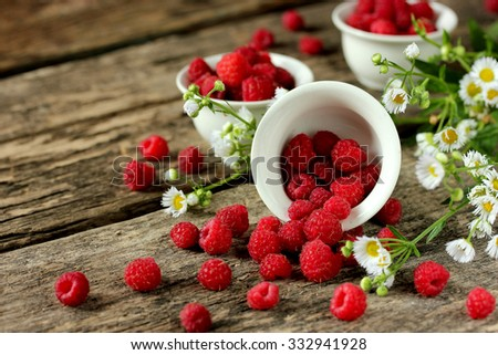 Fresh raspberries and daisies on a wooden table - stock photo