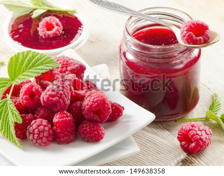 Fresh raspberries and jam .Selective focus - stock photo