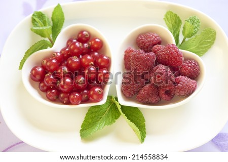 Fresh raspberries and red currant in Valentine's day - stock photo