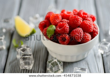 fresh raspberries in a white bowl on a wooden table - stock photo