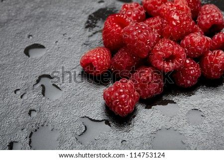 Fresh raspberries on a wet and black kitchen surface - stock photo