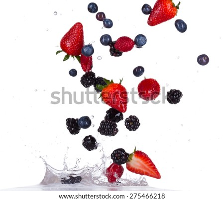 Fresh raspberries, strawberries, blackberries and blueberries in water splash isolated on white background - stock photo
