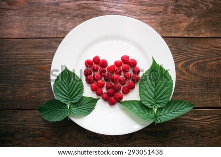 Fresh raspberry and leaves of raspberry lie on a white plate. Red heart from ripe berries. A studio photo on a dark wooden background. - stock photo