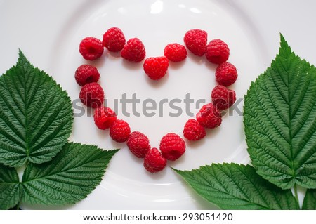 Fresh raspberry and leaves of raspberry lie on a white plate. Red heart from ripe berries. Studio photo. - stock photo