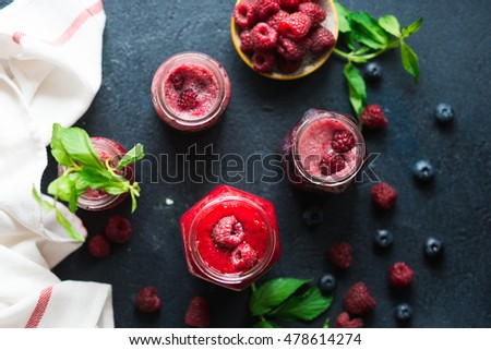 Fresh raspberry fruit drink in glass jar decorated by mint leaves and berries . Detox, diet or healthy food concept