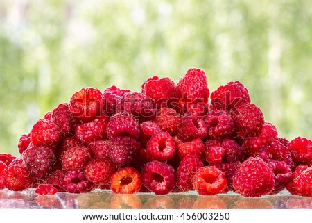 Fresh raspberry fruits on a glass table. Can be used as background       - stock photo
