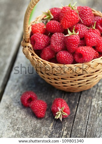fresh raspberry in a basket on wooden table - stock photo
