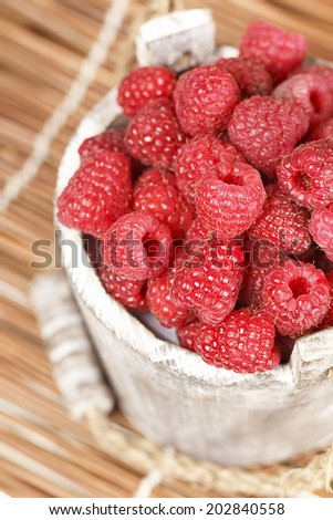Fresh raspberry in the wooden bucket - stock photo