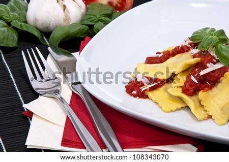 Fresh Raviolis on a plate with raw ingredients in the background on a black tablecloth