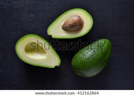 Fresh, raw avocado on a black background, top view  - stock photo