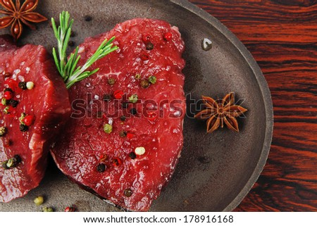 fresh raw beef fillet mignon on old retro style cast iron pan over retro wood table as background - stock photo