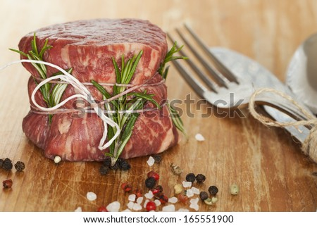fresh raw beef fillet mignon on old  wooden background  - stock photo