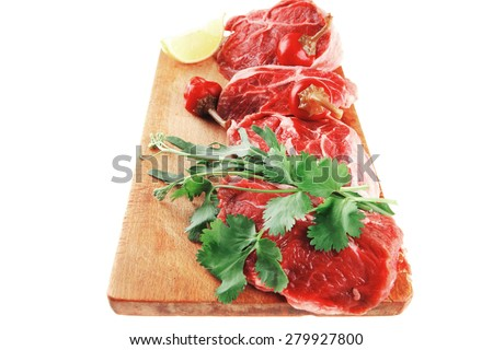 fresh raw beef meat medallion chunks on wooden plate isolated over white background with red hot peppers - stock photo