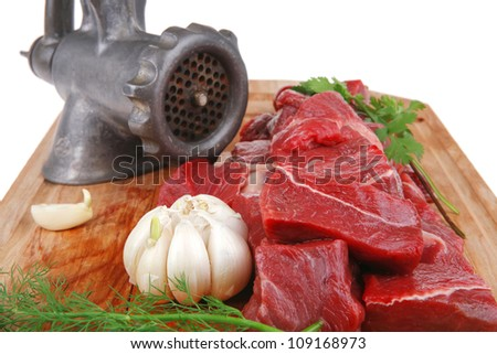 fresh raw beef meat slices over a wooden board with dill , green  and red hot peppers, and grinder isolated over white backkground