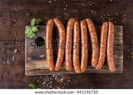 Fresh raw beef sausages with spices for BBQ on wood chopping board over dark wooden background with salt, herbs and pepper. Top view. - stock photo