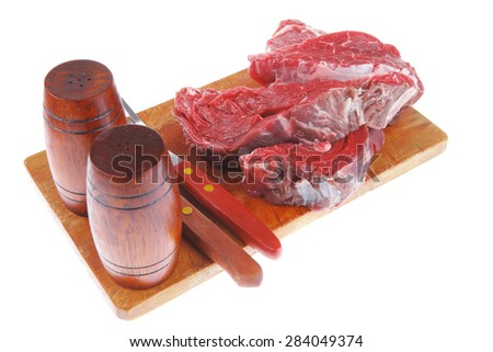 fresh raw beef steak entrecote fillet ready to prepare on cut board with cutlery and castor isolated over white background - stock photo
