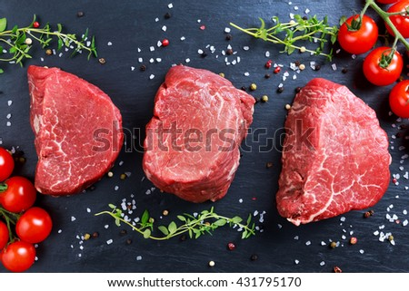 Fresh Raw Beef steak Mignon, with salt, peppercorns, thyme, tomatoes. - stock photo