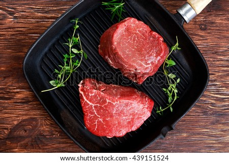 Fresh Raw Beef steak Mignon with thyme on grilled pan - stock photo