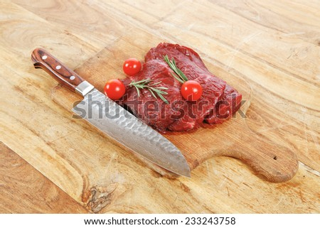 fresh raw beef steak with cherry tomatoes rosemary twig on wood cut plate over table with japanese layered stainless steel knife - stock photo