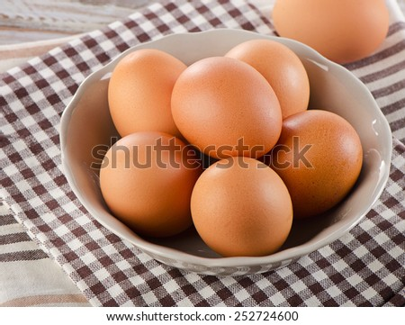 Fresh  raw brown eggs in a bowl. Selective focus