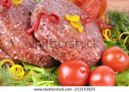 Fresh raw burger cutlet with herbs pepper and tomatoes - stock photo
