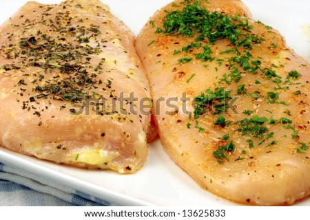fresh raw chicken breast seasoned with pepper and aromatic parsley