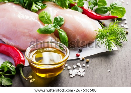 Fresh raw chicken breast, spices and herbs on black background - stock photo