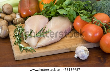 Fresh raw chicken fillets and vegetables prepared for cooking - stock photo