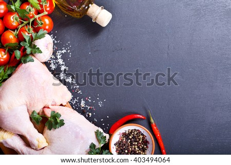 fresh raw chicken legs with vegetables on dark background - stock photo