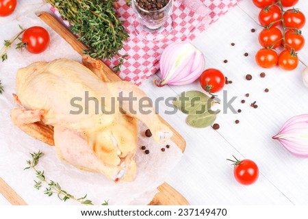 Fresh raw chicken prepared for roast with thyme and tomatoes cherry - stock photo