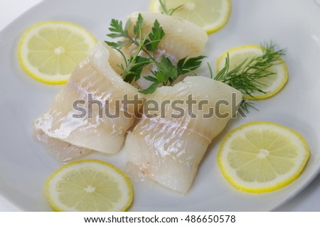 fresh raw cod fish fillet on a plate with parsley and lemon