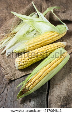 Fresh raw corn on wooden table