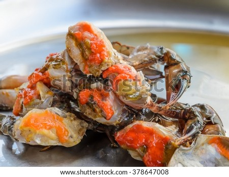 Fresh raw female crab marinated in fish sauce on stainless steel serving tray. Thai street food. - stock photo
