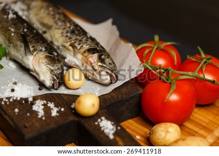 Fresh raw fish and ingredients on wooden table - stock photo