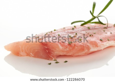 Fresh raw fish fillet with fresh green herbs isolated on white background. Culinary seafood eating.